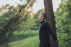 Photo of man standing next to tree in a forest