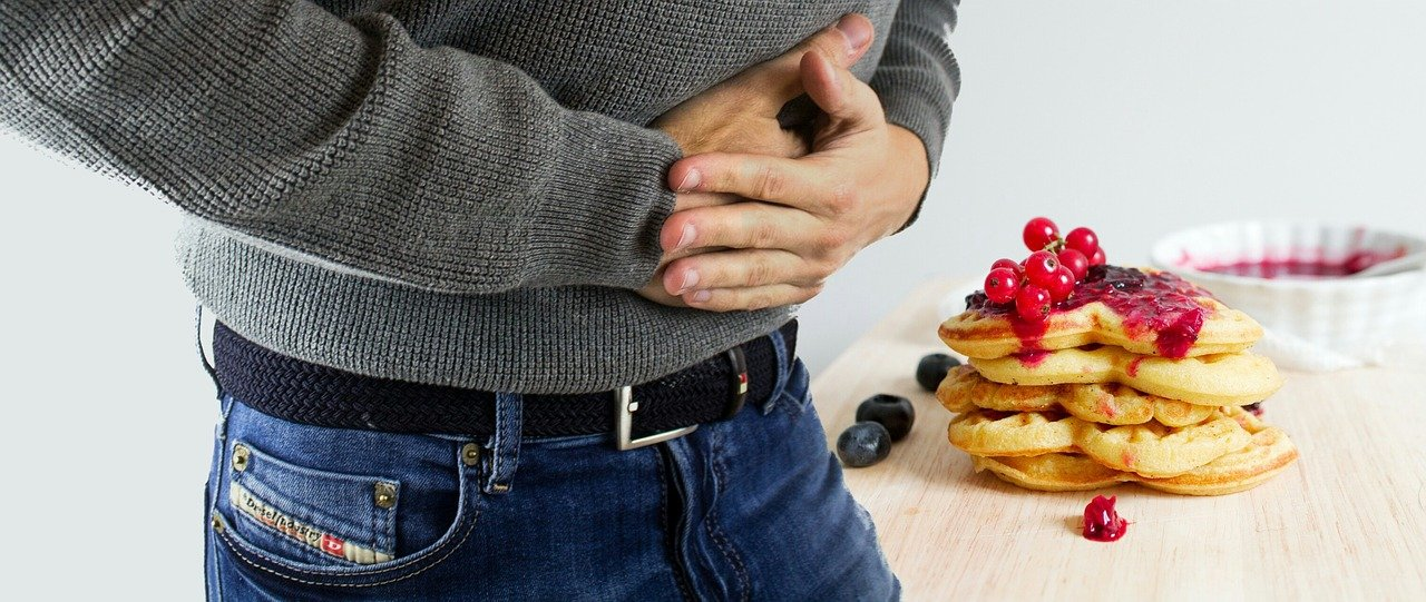 Man with stomach ache holding his belly